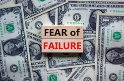 Fear of failure symbol. Wooden blocks with words 'fear of failure'. Beautiful background from dollar bills, copy space. Business, fear of failure concept.