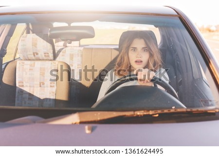 Fearful driving woman, learns to drive automobile, attractive female sits at wheel alone for first time, tries to avoid car accident, has frightened facial experessions, wants to stop vehicle. #1361624495