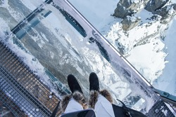Fearful glass floor at the popular attraction, Thrill walk at Birg, 2677m on the way to Schilthorn Piz Gloria, Lauterbrunnen in winter. Woman standing looking down at the snowy Switzerland mountain