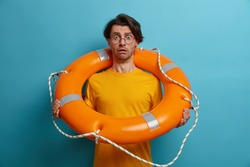 Fearful man afraids of swimming in deep sea, poses with inflated lifebuoy, listens advice of instructor, wears spectacles and glasses, poses against blue background. Guy lifesaver holds buoy ring