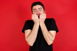 Fearful Young caucasian man wearing black t-shirt over red background keeps hands near mouth, feels frightened and scared,  has a phobia,  Shock and frighted concept.
