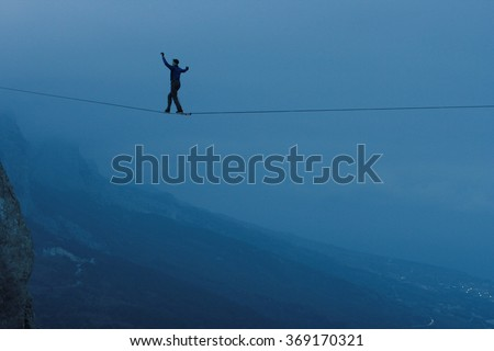 Fearless highliner walking on tight rope. At the height of mountains in the background