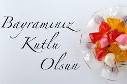 Feast concept, Traditional Turkish Ramadan sweet sugar candy, colorful akide sekeri in glass bowl. Writing near Feast Greeting or Happy Holliday in Turkish (Translation: Bayramınız kutlu olsun)