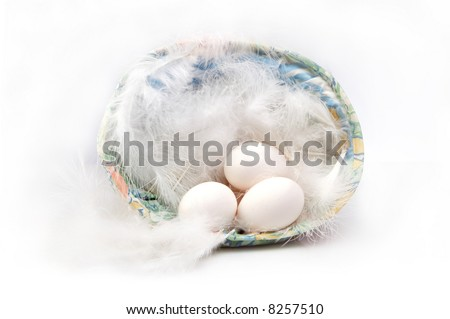 Feathers and three white chicken eggs in an easter basket #8257510