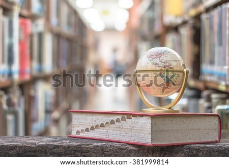 FEBRUARY 26, 2016 - BANGKOK, THAILAND: Globe model on textbook, or dictionary on  table in school or university library educational resource for knowledge