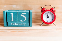 February 15. Blue cube calendar with month and date on wooden background.