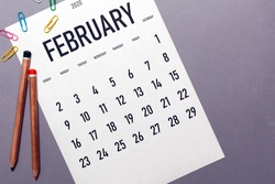 February 2020 simple calendar with office supplies and copy space