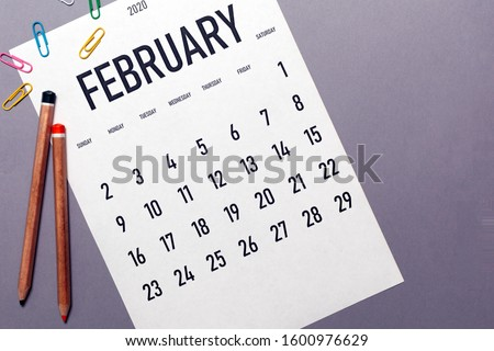 Photo of  February 2020 simple calendar with office supplies and copy space