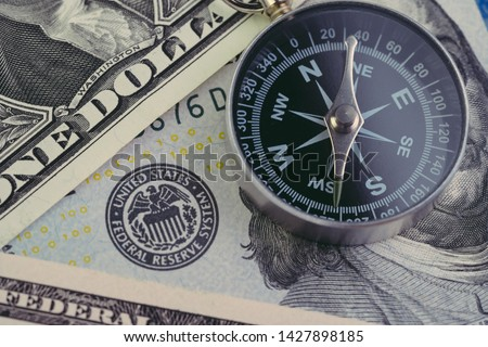 FED, Federal Reserve of US government direction on interest rate concept, compass on US Dollar banknote with Feral Reserve emblem.