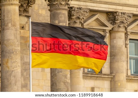 Federal Republic of Germany, German national flag waving in front of the Parliament building columns