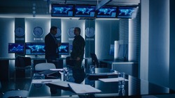 Federal Special Agent Talks To Military Man in the Monitoring Room. In the Background Busy System Control Center with Monitors Showing Data Flow.