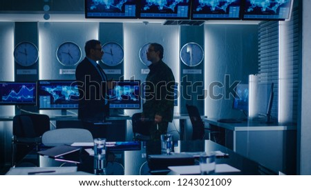 Federal Special Agent Talks To Military Man in the Monitoring Room. In the Background Busy System Control Center with Monitors Showing Data Flow. #1243021009