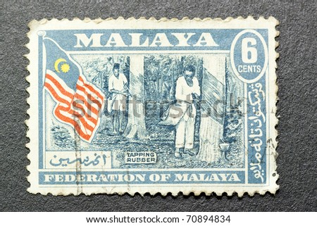 FEDERATION OF MALAYA - CIRCA 1961: A stamp printed in the Federation of Malaya shows image of the Malaysian flag and Tapping Rubber activity, series, circa 1961