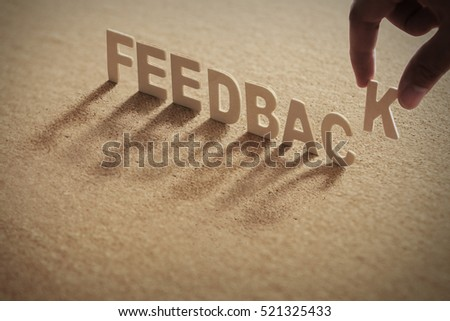 FEEDBACK wood word on compressed board,cork board with human's finger at K letter #521325433