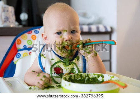 Feeding. Adorable baby child eating with a spoon in high chair. Baby\'s first solid food