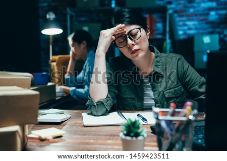Feel exhausted. Frustrated young asian woman keeping eyes closed while sitting at working place at night time frown suffer headache. coworkers in e commerce office startup small business overworked #1459423511