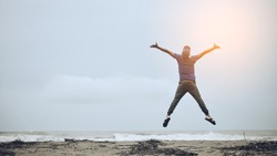 Feel good and freedom concept. Copy space of happy man jumping on beach. Vintage tone color style.