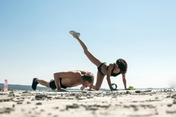 Feel good and freedom concept. Young handsome strong man raising hands up on the beach against sky. Athletic man and woman doing fitness exercise. Couple in love. Fitness concept. Sport. Fashion.