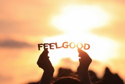 FEEL GOOD text in hands on the sunset sky