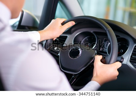 Feel the drive. Selective focus of hands of professional sale assistant sitting in the car at the wheel while testing  the car #344751140