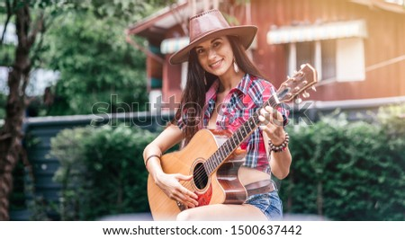 Feel the lifestyle. Beautiful cowgirl singer perfoming outdoors. Copy space on the right and on the left side