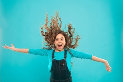 Feeling active and energetic. Energetic little girl with long brunette hair on blue background. Active small child with cute look being in energetic mood. Energetic style.