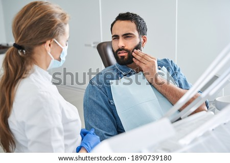Feeling bad. Young multiracial man having toothache, sitting in a dental chair at the clinic. Bearded male patient with terrible toothache visiting dentist. Stock photo Сток-фото ©