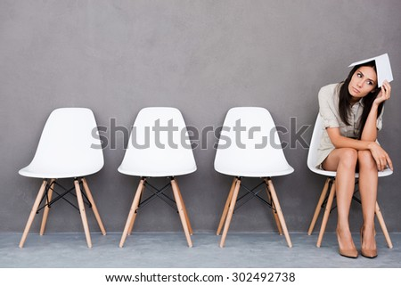 Feeling bored of waiting. Bored young businesswoman holding paper on her head and looking away while sitting on chair against grey background