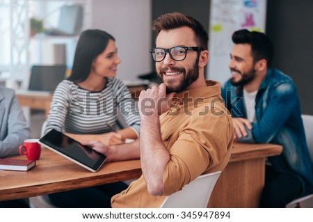 Feeling confident in my team. Group of business people in smart casual wear discussing something while one man holding digital tablet and looking over shoulder with smile