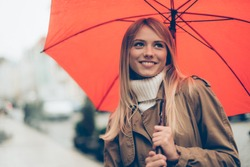 Feeling dry and protected. Attractive young woman carrying umbrella and smiling while standing on the street