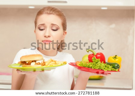 Feeling embarrassed. Beautiful lady holding plate with fast-food in one hand and vegetables in another feeling temptation to eat sandwich
