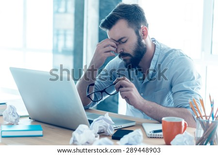 Feeling exhausted. Frustrated young beard man massaging his nose and keeping eyes closed while sitting at his working place in office