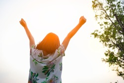 Feeling free. Upper body shooting from rear and low angle view of a young girl standing outdoor raising her arms up to sky to express good feeling. Image with copy space.