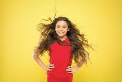 Feeling good fabulous hair. Adorable small girl smiling with long brunette hair. Happy child with flowing hair on yellow background. Little kid with cute smile and wavy textured hair.
