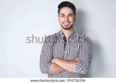 Feeling great! Beautiful brunette young man in casual shirt is smiling and crossed his arms over chest against light grey background