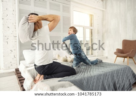 Feeling great. Nice joyful little fair-haired boy smiling and playing with his daddy at home and they having a pillow fight #1041785173
