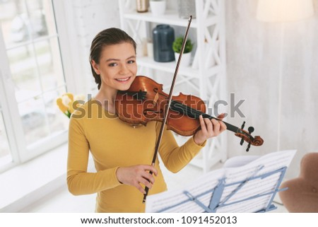 Feeling happiness. Attractive girl expressing positivity while holding her instrument