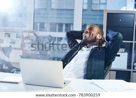 Feeling joy. Cheerful young elegant african businessman is reclining on chair and holding his hands behind head while looking up with wide smile