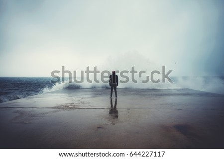 Feeling of freedom, back view of adult man standing on pier facing to the sea with big waves beats against the shore on a cloudy autumn day, alone depress person,the power of nature, storm on seashore #644227117