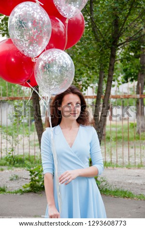 Feeling playful. playful young woman holding red balloon bouquet and smiling while standing against outdoor background #1293608773