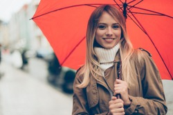 Feeling protected at rainy day. Attractive young woman carrying umbrella and looking at camera with smile while standing on the street