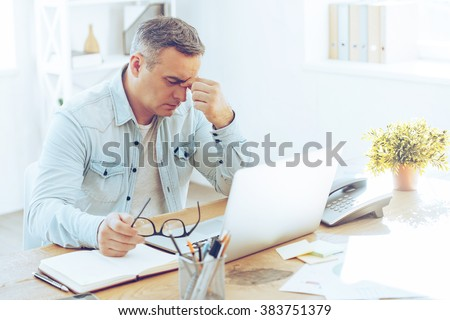 Feeling sick and tired. Frustrated mature man looking exhausted while sitting at his working place and carrying his glasses in hand #383751379