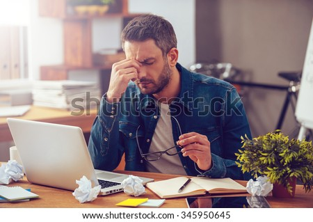 Feeling sick and tired. Frustrated young man massaging his nose and keeping eyes closed while sitting at his working place in office