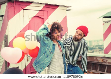 Feeling sleepy. Tired bearded man looking at his girlfriend standing with her eyes closed and holding balloons after the party #1189780936