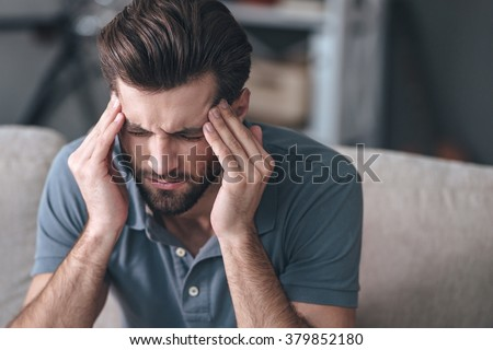 Feeling stressed. Frustrated handsome young man touching his head and keeping eyes closed while sitting on the couch at home #379852180