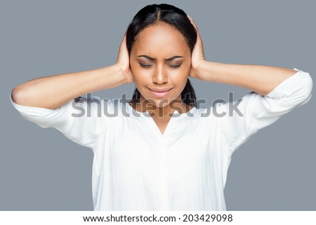 Feeling tired and stressed. Frustrated young African woman covering ears with hands and keeping eyes closed while standing against grey background