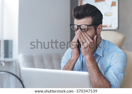 Feeling tired. Frustrated young handsome man looking exhausted and covering his face with hands while sitting at his working place  #370347539
