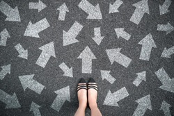 Feet and arrows on road background. Woman standing with many direction sign arrow choices in different ways, left and forward. Taking decisions for the future female. Top view of selfie foot and shoe.