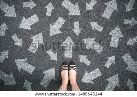 Feet and arrows on road background. Woman standing with many direction sign arrow choices in different ways, left and forward. Taking decisions for the future female. Top view of selfie foot and shoe. #1480645244
