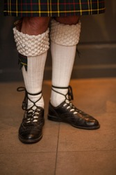 Feet and legs in Scottish skirts, a Scottish traditionally dressed bagpiper plays on St. Patrick's Day, holiday costumes for men. High quality photo